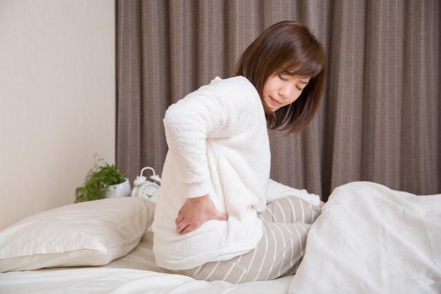 寝起き時の辛い腰痛に悩む女性